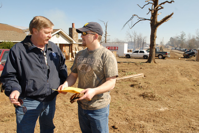Atkins, AR, February 9, 2008 -- A FEMA public information officer gives information to a resident impacted by the recent tornadoes.  Jocelyn Augustino/FEMA
