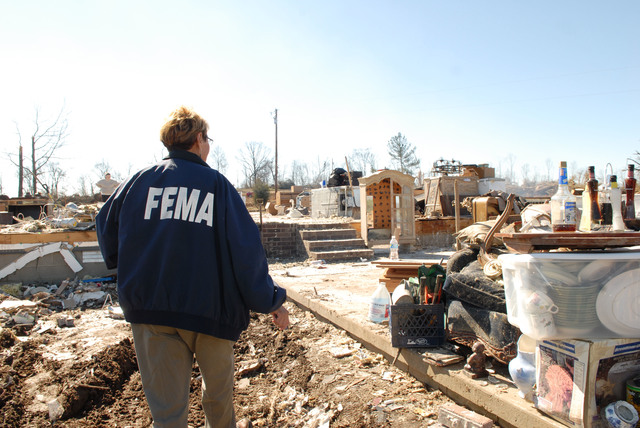 [Severe Storms, Tornadoes, and Flooding] Atkins, AR, February 9, 2008 -- A FEMA Community Relations representative walks through a damaged neighborhood looking for residents.  FEMA CR workers try to distribute information on where to get assistance and how to apply for aid. Jocelyn Augustino/FEMA
