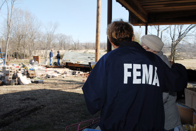 [Severe Storms, Tornadoes, and Flooding] Atkins, AR, February 9, 2008 -- A FEMA Community Relations representative speaks with a resident in a damaged neighborhood.  FEMA CR workers meet with residents to give them information on where to get assistance and how to apply for aid. Jocelyn Augustino/FEMA