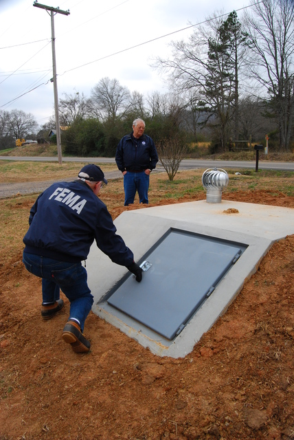 [Severe Storms, Tornadoes, and Flooding] Atkins, AR, February 26, 2008  -– FEMA Public Information Officer, Nate Custer, left, and Resource Manager, Sterling Rich examine a newly installed storm shelter North of Atkins.  After witnessing the destruction from the Feb. 5 tornado the owner started construction on this shelter the next day.  Charles S. Powell/FEMA