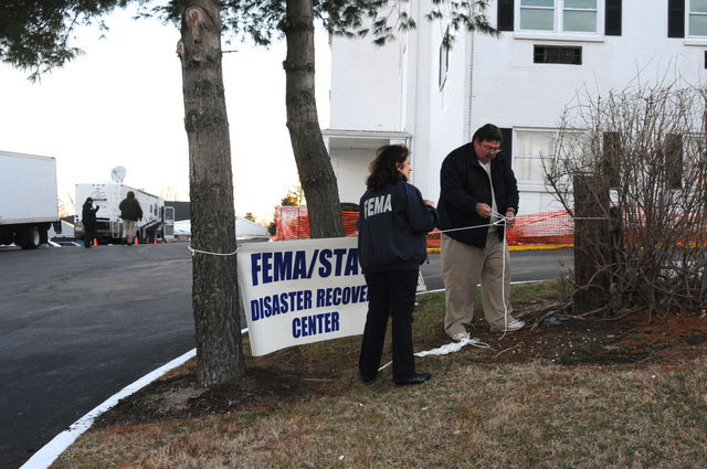 [Severe Storms, Tornadoes, Straight-line Winds, and Flooding] Lexington, KY, March 3, 2008 -- This FEMA Mobile Disaster Recovery Center(MDRC) sign is being set up by MDRC Manager Vivian Barrios and MDRC driver Greg Morrison in preparation for the Center's opening today. FEMA is here in response to severe storm and tornado which impacted this county (Fayette) in early February.  George Armstrong/FEMA