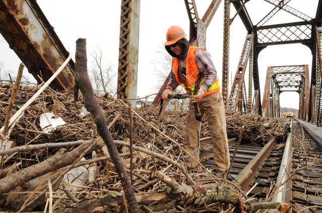 [Severe Storms and Flooding] Valley Park, MO, March 23, 2008 -- A railroad worker removing debris from the tracks on a  railroad bridge passing over the Meramec River.  The debris was left on the bridge as a result of  the recent rise in the river.  Jocelyn Augustino/FEMA