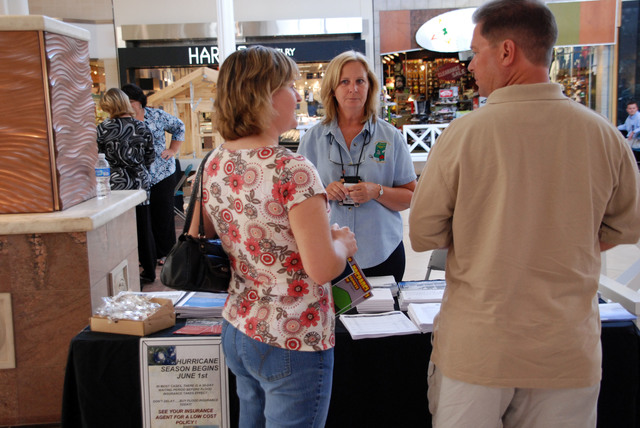 """[Hurricane Katrina] Biloxi, MS, June 6, 2008 -- Greg and Ashley White talk to NFIP Insurance Specialist Diana Kidder and look at information at a Hurricane Expo at Edgewater Mall. FEMA provided educational materials and exhibited the mitigation """"dawg house"""" to educate people at the expo, which marked the first week of hurricane season. Jennifer Smits/FEMA."""