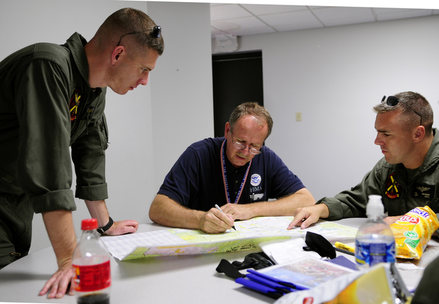 [Severe Storms, Tornadoes, and Flooding] Cedar Rapids, IA, June 19, 2008 -- Marine Helicopter Squadron-1 (HMX-1) pilots, Maj. Wade Dunford (L) and Capt. Brian Gahgan chart the route they will fly the President Bush; DHS Secretary Chertoff; Iowa Governor Culver and FEMA Administrator, Paulison when  they take an aerial tour of flooded areas of Iowa with FEMA Region VII Administrator, Dick Hainje.  Barry Bahler/FEMA