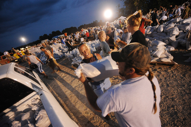 Winfield, MO, 06/19/2008 -- Local volunteers prepare sandbags into the evening hours at a local high school to help sandbagging efforts on the local levees in anticipation of breaching of the levees.  Jocelyn Augustino/FEMA