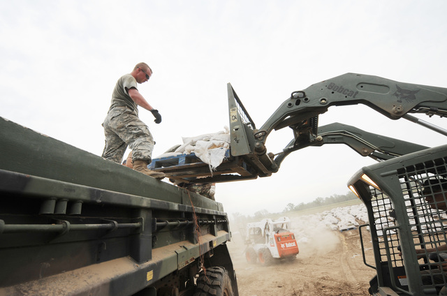 Winfield, MO, June 19, 2008 -- Members of the Missouri National Guard, Army and Air Force National Guard stack sandbags on a truck that will transport the sandbags next to the levee in anticipation that the levee may breach.  They have stacked well over two and a half miles of sandbags on the levee.  Jocelyn Augustino/FEMA