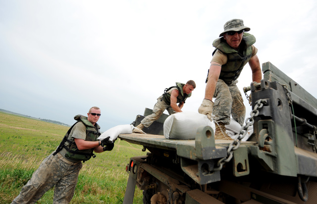 Winfield, MO, June 19, 2008 -- Members of the Missouri National Guard, Army and Air Force National Guard stack sandbags next to the levee in anticipation that the levee may breach.  Jocelyn Augustino/FEMA