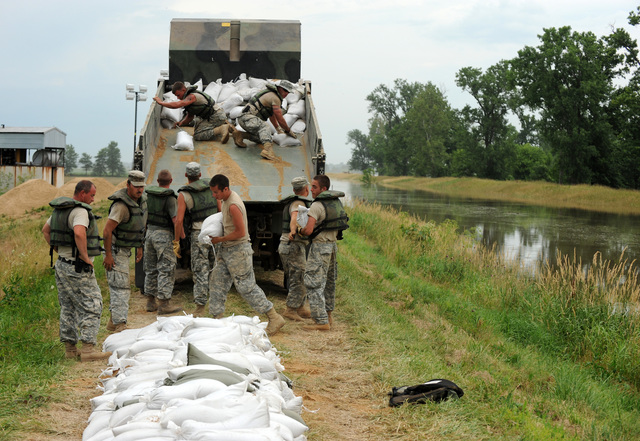Winfield, MO, June 19, 2008 -- Members of the Missouri National Guard, Army and Air Force National Guards unload sandbags from a truck and stack them on the levee in anticipation of higher food water.  Jocelyn Augustino/FEMA