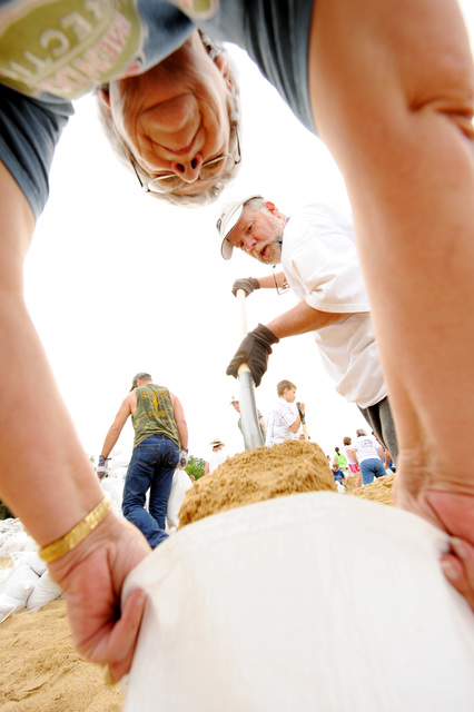 Winfield, MO, June 19, 2008 -- Volunteers Patrick Dougherty, with shovel, and Toni Drew prepare sandbags at a local high school to help for sandbagging efforts at the local levees  on June 19, 2008.  Jocelyn Augustino/FEMA