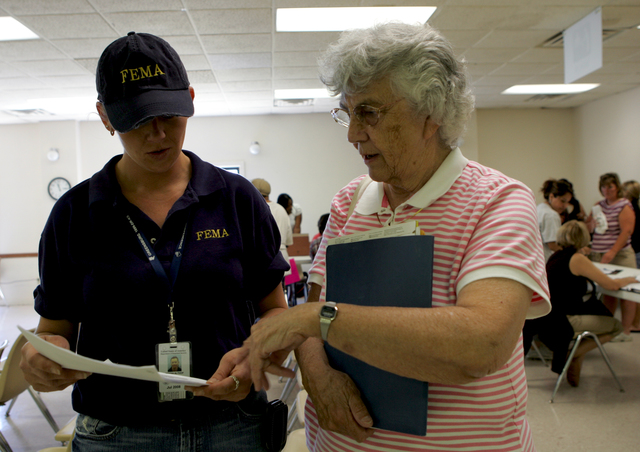 [Severe Storms, Tornadoes, and Flooding] Wapello, Iowa, June 28, 2008 -- Donna Althof, Manager of the FEMA/State  Disaster Recovery Center, explains to Benita Grooms, the Mayor of Oakville how to apply for FEMA disaster assistance. The Mayor's home and most of her belongings were destroyed in the flood two weeks ago. Susie Shapira/FEMA