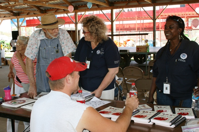 [Severe Storms, Tornadoes, and Flooding] Corning, Iowa, July 13, 2008 -- FEMA Community Relations Representatives Sally Fenley and Quinzenia Mack answer questions from local farmers at the Adams County Fair.  Adams County suffered from the recent June floods and is on the declared disaster list. Judith Grafe/FEMA