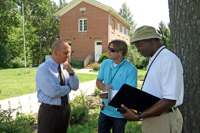 [Severe Storms, Tornadoes, and Flooding] Coralville, IA, July 15, 2008 -- Johnson County Historical Society Executive Director Shamer Magalhaes provided some background on the historic 1876 school building to FEMA Public Assistance Project Specialist Allen Davis and Building Assessment Team member Tommy Kwia. Several key Coralville buildings were damaged by last month's major flood.  Photo by Greg Henshall / FEMA