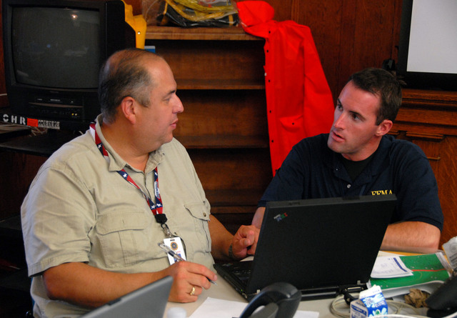 Brownsville, Texas, July 23, 2008 -- FEMA official Derek Shackelford and Cameron County Emergency Manager Johnny Cavazos discuss emergency response needs  in response to Hurricane Dolly at the Cameron County Emergency Operations Center.  FEMA Photo / John Shea.