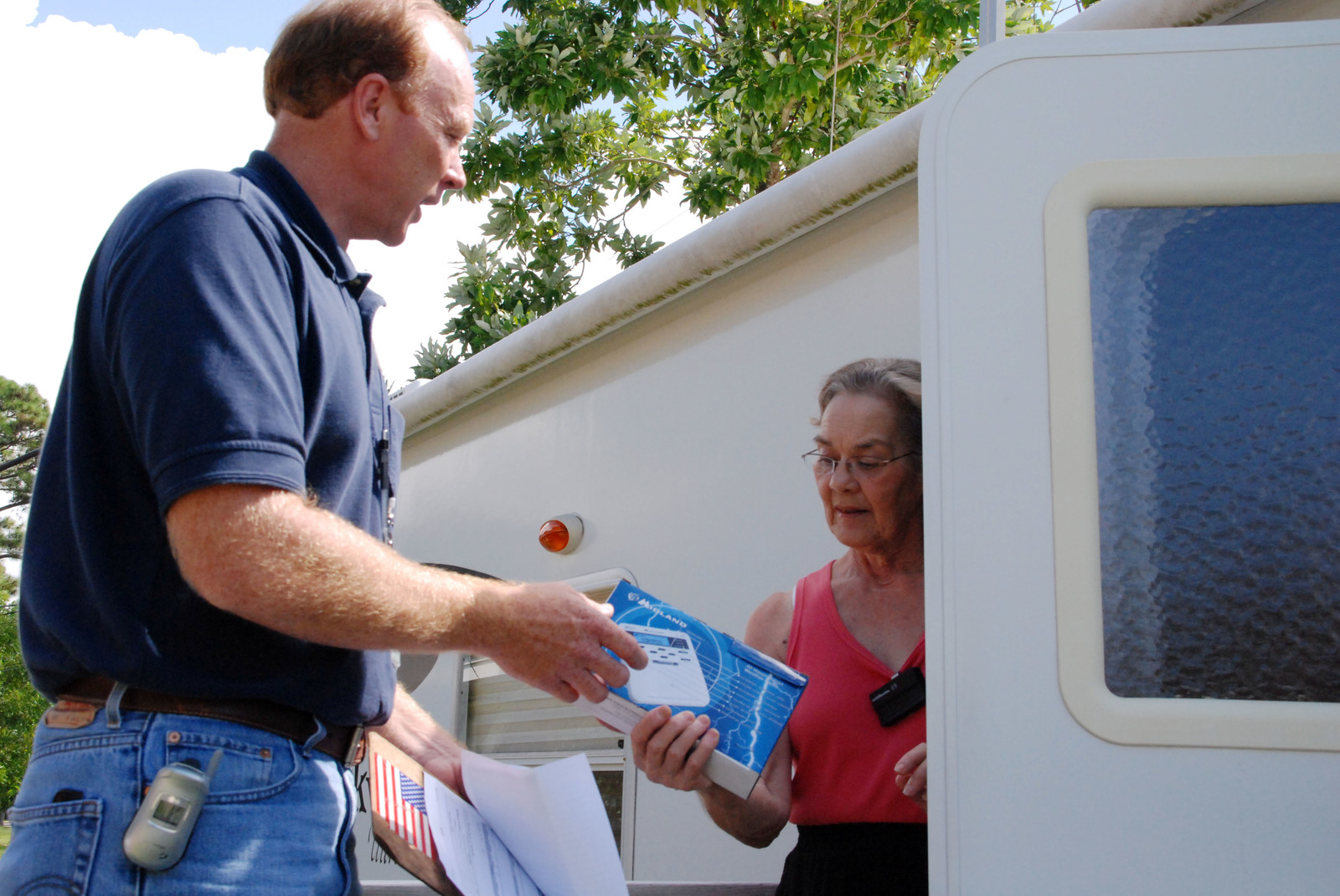 [Hurricane Katrina] Pascagoula, MS, July 31, 2008 - -FEMA housing advisor Bobby Russell gives a NOAA Weather Radio to Gloria Thompson. FEMA is issuing weather radios to all applicants still living in FEMA travel trailers and mobile homes in Mississippi. Jennifer Smits/FEMA.