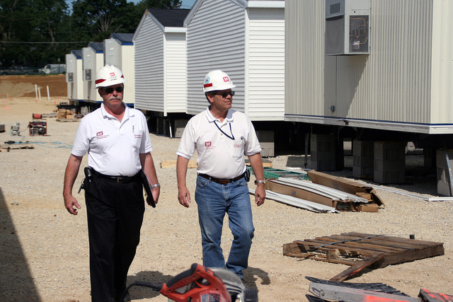 [Severe Storms, Tornadoes, and Flooding] Cedar Rapids, IA, August 6, 2008 -- Jim Mosner and Dick Otto, Mission Managers for the U.S. Army Corp of Engineers, check  progress on the school administration buildings being installed on the grounds of Kingston Stadium.  FEMA asked the Corp to install thirty-five modular units by the middle of August for the Linn County Board of Education, which lost the use of its building in the June flood.  Photo by Greg Henshall / FEMA