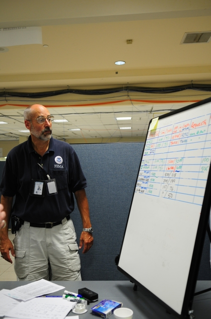 [Hurricane Gustav] Baton Rouge, LA, September 1, 2008 -- David Hirtle, manager of FEMA's Emergency Support Function 6 (ESF-6), Shelter Management Flow briefs staff from his flow chart of the seventy-four shelters activated state wide, with capacity of 45,332 of which 32,323 occupants were utilizing during Hurricane Gustav.  Barry Bahler/FEMA