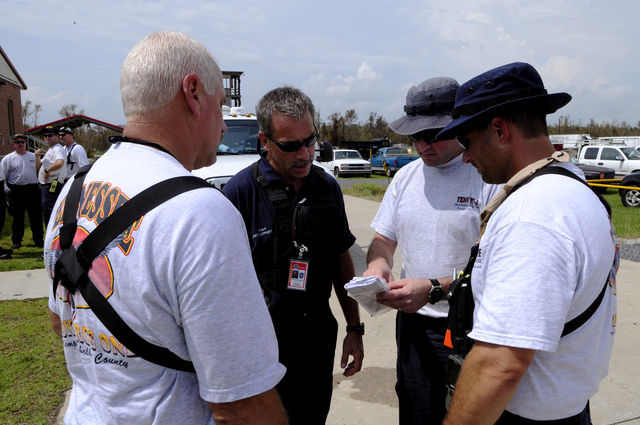 [Hurricane Gustav] Chauvin, LA, September 4, 2008 --  Members of the Tennessee Urban Search and Rescue Task Force 1 (TN TF-1), Memphis discuss what they saw while conducting Search and Rescue (USAR) operations in the remote parts of Terrebonne Parrish, with a manager of the FEMA Incident Management Assistance Team (IMAT). Coordination between local, state and federal teams is crucial in USAR.  Barry Bahler/FEMA