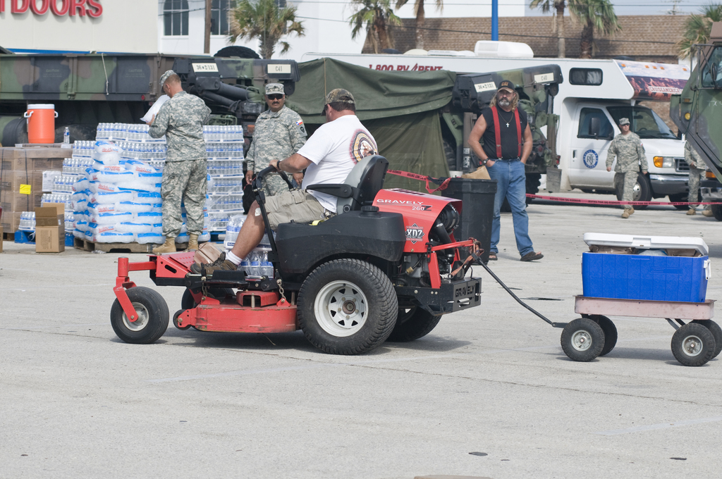 [Hurricane Ike] Galveston Island, TX, September 15, 2008 -- A resident of Galveston Island who chose to ride out the storm, gets ice, food and water at a POD site. The tractor driving resident provided a moment of laughter for the soldiers working the site.  Photo by Patsy Lynch/FEMA