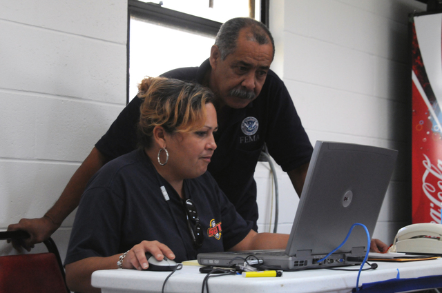 [Tropical Storm Fay] Moore Haven, FL, September 15, 2008 -- The Glades County FEMA Disaster Recovery Center(DRC) State Manager Maribel Martinez checks computer operations with FEMA Individual Assistance(IA) Lead Wilfredo Dominguez as the DRC prepares to open today.  FEMA and State are partners in helping residents affected by Tropical Storm Fay.  George Armstrong/FEMA