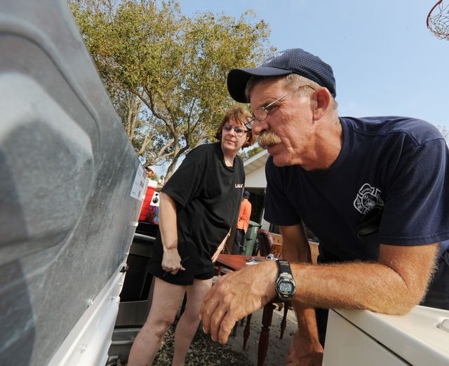 [Hurricane Ike] Galveston Island, TX, September 19, 2008 -- Galveston Fire Fighter Tom Boone gets the serial number off of one of his major appliances for his wife Betty, to keep a record  for the insurance company after fellow fire fighters help get items out of his house.  Boone's house was flooded from Hurricane Ike.  Jocelyn Augustino/FEMA