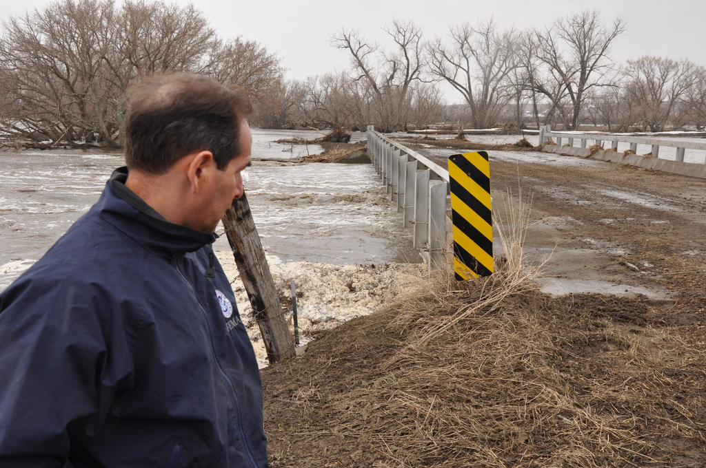 Flooding ^ Winter Storm - Morton County, N. D. , April 13, 2009 -- Morton County, ND, April 13, 2009 -- Fast moving, swollen Big Muddy Creek ripped the road out at the east end of this rural area bridge.  Field PIO Art Alejandre views the creek as it was hitting the bottom of the concrete bridge.  Michael Raphael/FEMA