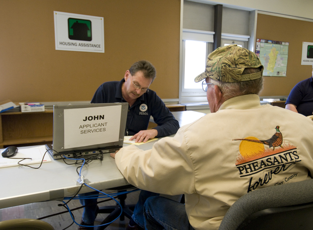 Flooding ^ Severe Storm - Moorhead, Minn. , April 15, 2009 -- Individual Assistance (IA) Specialist John Shrum helping an applicant in the first moments after the Moorhead Disaster Recovery Center (DRC) opening. FEMA operates DRCs near disaster areas to assist a community affected by a disaster. Mike Moore/FEMA