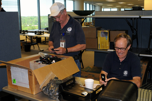 Flooding ^ Severe Storm - Atlanta, Ga. , April 26, 2009 -- At the soon-to-be-opened FEMA/State Joint Field Office (JFO), Logistics Specialist Dexter Spalding and IT Telecom Manager Thomas Crane prepare telephones for distribution. A Federal Disaster Declaration was signed April 23 for 27 Georgia Counties as result of severe storms, flooding, tornadoes and straight line winds beginning on March 26. FEMA and State workers will report to this location for equipment and assignment. George Armstrong/ FEMA