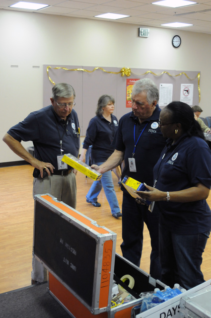 "Flooding ^ Severe Storm - Tallahassee, Fla. , May 13, 2009 -- At the Leon County FEMA/State Disaster Recovery Center(DRC), FEMA Safety Officer Walter Newbury(C) checks to see that there is a functioning weather radio and first aid kit as Safety Officer Fred Curtis, and FEMA DRC Manager Charlanne ""Chi Chi"" Jackson observe. FEMA Safety Officers must do an initial assessment before DRC opening, again on the first day of operation, and then twice a week to be certain that those seeking help from recent storms/flooding, as well as DRC staff are safe.  George Armstrong/FEMA"