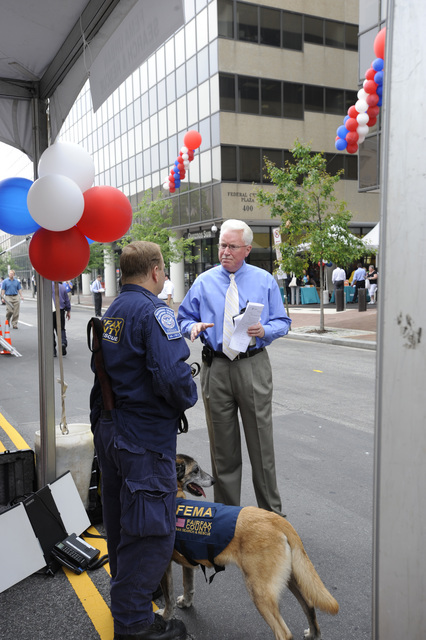 Washington, D. C. , June 11, 2009 -- FEMA's Acting Deputy Administrator David Garratt speaks with Ron Sanders from Virginia's Urban Search and Rescue Task Force 1 in Fairfax County with his dog Ondo.  This is FEMA's 4th Annual Safety and Preparedness Expo and this year it's on the street in front of FEMA Headquarters.  FEMA/Bill Koplitz