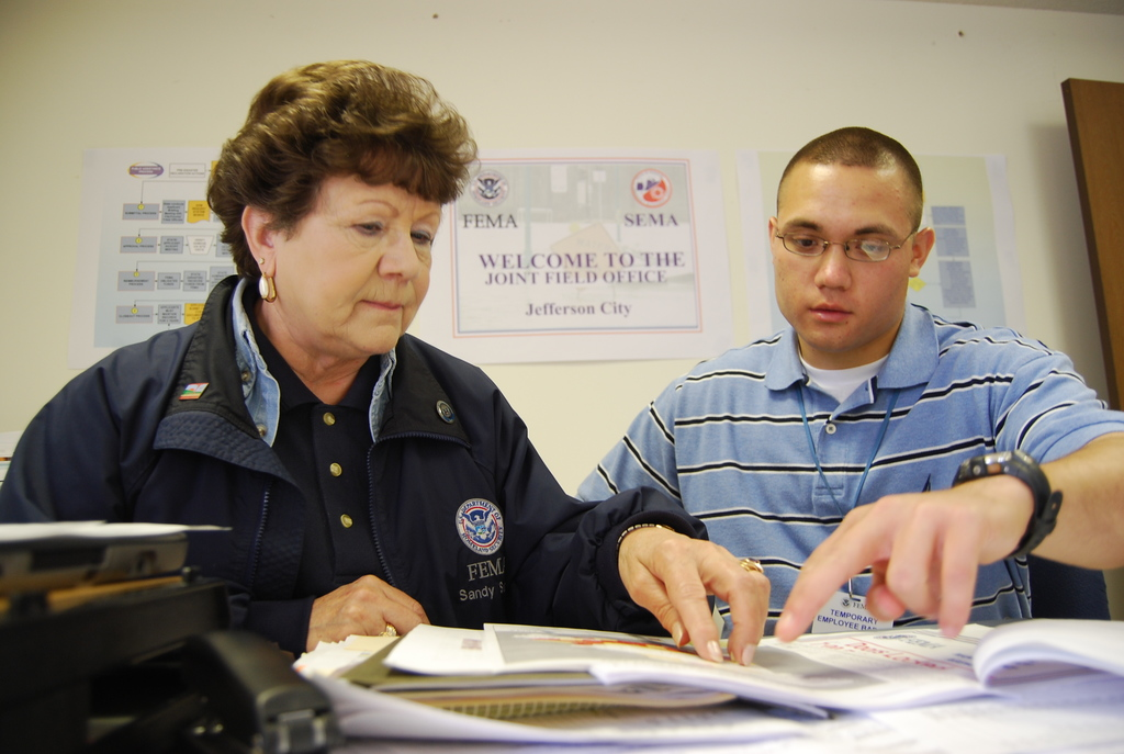Flooding ^ Severe Storm ^ Tornado - Jefferson City, Mo. , June 30, 2009 -- Sandy Sunde, planning section chief for the Joint Field Office (JFO) for the Federal Emergency Management Agency (FEMA), gives West Point Cadet Peter Rome an overview of the Planning section and required reports for disaster response. Rome spent three weeks interning with FEMA visiting a JFO, seeing first-hand how FEMA responds to disasters.