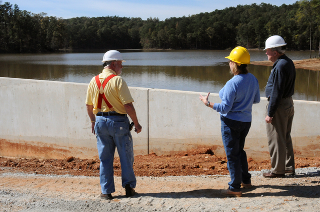 Dam/Levee Break ^ Flooding ^ Severe Storm - Douglasville, Ga. , October 21, 2009 -- At the Douglas County Dog River Reservoir FEMA Public Assistance Coordinator Pressly Beaver(left), County Water and Sewer Authority Project Engineer Kathy Macias, and FEMA Technical Assistance Contractor Frank Lockridge are reviewing areas of the dam which failed during the September severe storms and flooding. FEMA Public Assistance funds have been requested to pay a share of repair costs. George Armstrong/FEMA