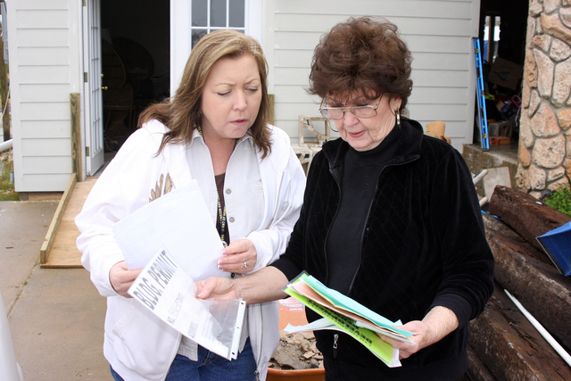 Hurricane/Tropical Storm - Hitchcock, Texas, January 20, 2010 -- FEMA Individual Assistance Applicant Services Specialist Lisa Jackson reviews paperwork with Barbara Dowden regarding her recent purchase of the temporary housing unit FEMA provided to the Dowdens for use as they made repairs to their Hurricane Ike damaged home. They will continue to use the unit located on their property as repairs continue. Robert Kaufmann/FEMA