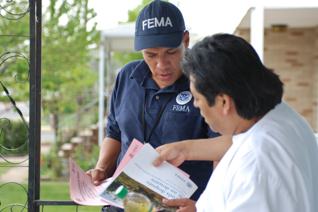 Flooding - Bound Brook, N. J. , April 21, 2010 -- Community Relations specialist Byron Rivera explains the FEMA registration process to Adelfo Flores in a Hispanic community in Bound Brook. FEMA offers a multilingual registration process for the affected residents in New Jersey. Michael Medina-Latorre/FEMA