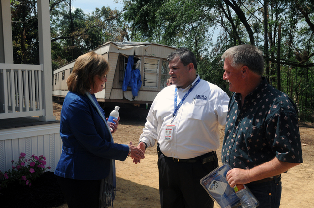 """Severe Storm ^ Tornado - Yazoo, Miss. , May 14, 2010 -- Mrs. Marsha Barbour, wife of Governor Haley Barbour greets Mississippi Emergency Management Agency Individual Assistance Housing Specialist John Garcia as the first Yazoo City """"Mississippi Cottage"""" purchaser Eddie """"Butch"""" Ketchum looks on. The unique MEMA """"Cottage"""" program is a purchase not a lease, is a built house, and not intended to be only temporary housing for storm survivors left homeless in the April 24 tornado. FEMA and MEMA are partners in disaster recovery efforts such as this. George Armstrong/FEMA"""