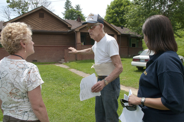 Flooding - Olive Hill, Ky. , June 2, 2010 -- FEMA Mitigation specialist Kathi Merritt and Admin specialist Sandra Draper talk to 90 year old resident Carl Mullins and hand out FEMA fliers for an event to be held on Saturday June 5. Flooding devastated many areas in Kentucky in early May. Photo by Liz Roll/FEMA