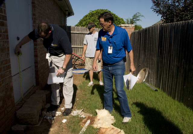 Flooding - Edmond, Okla. , June 18, 2010 --Fred Barnes, an Oklahoma emergency management official measures the height that flood waters reached when the Edmond, OK area was flooded on Monday, June 14,2010.  Richard Warthen, an SBA construction specialist looks on.  FEMA is working with local and state officials to determine whether Oklahoma will be eligible for federal assistance after a record amount of rain caused flooding in the area.  Photo by Patsy Lynch/FEMA