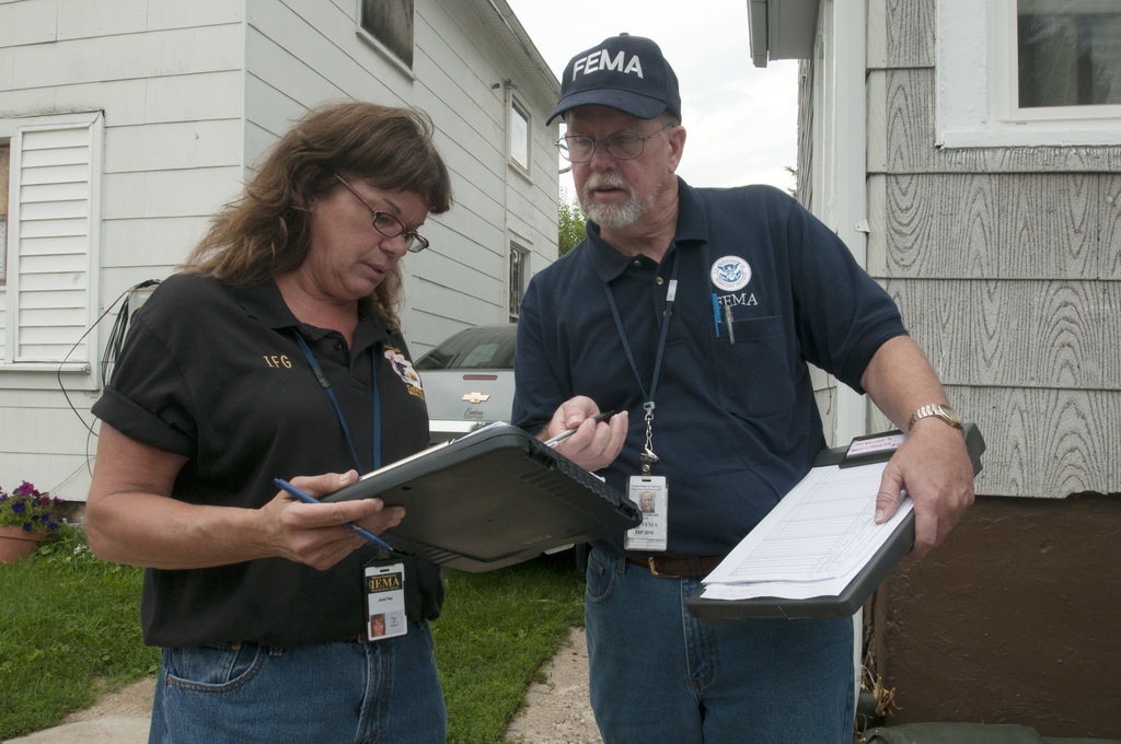 Flooding - Freeport, Ill. , August 4, 2010 -- Janet Pate, an Illinois Emergency Management Agency IEMA representative  and Patrick Fisher, a FEMA individual assistance specialist compare notes on a flooded house they inspected in an area of Freeport, IL.  FEMA is working with state and other federal agencies to assist residents and businesses affected by recent flooding. Photo by Patsy Lynch/FEMA