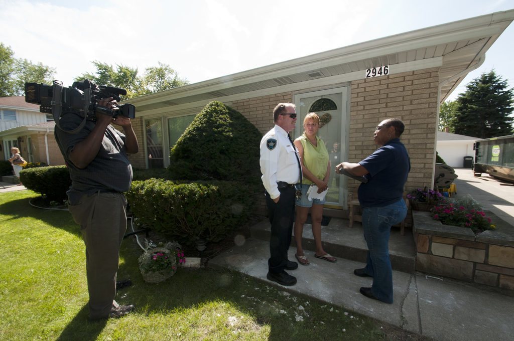 Flooding - Westchester, Ill. , August 9, 2010 --Tina White, a FEMA Individual Assistance specialist talks with Acting Westchester, IL police chief, Lt. Mike O'Hagan and his wife in front of their home.  Their home was flooded during the record rainfall in late July. A Chicago TV station was filming the first day of the preliminary damage assessment in the area. FEMA is working with the Illinois Emergency Management Agency (IEMA) to conduct preliminary damage assessment for the IL Governor's office.  Photo by Patsy Lynch/FEMA