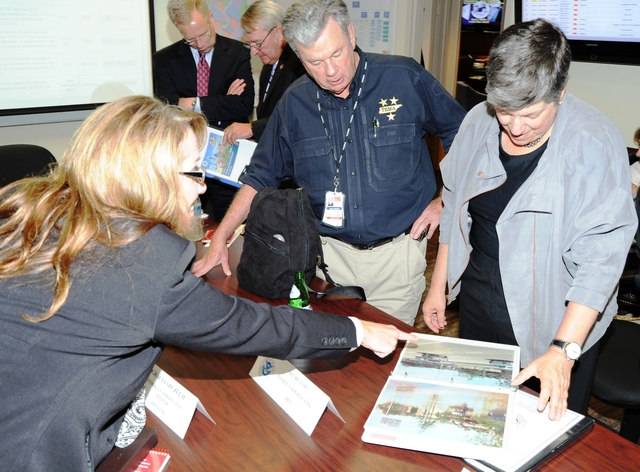 Flooding ^ Severe Storm ^ Tornado - Nashville, Tenn. , September 1, 2010 -- During a visit to Nashville, DHS Secretary Napolitano reviews before and after photos included in a report on the (DR-1909) storms, tornadoes and flooding that swept Tennessee beginning April 30.  Federal Coordinating Officer Gracia Szczech points out photo details as Tennessee Emergency Management Agency Director James Bassham looks on.  Mike Osborne/FEMA