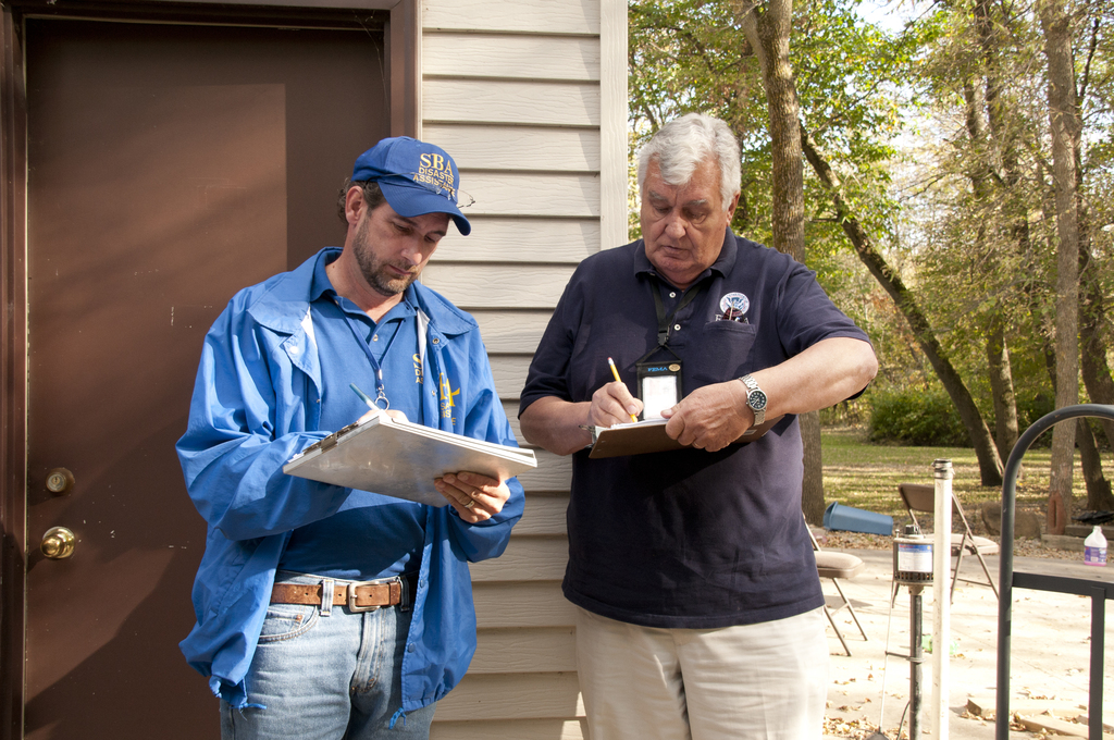 Flooding - Triton, Minn. , September 28, 2010 -- Rich Barto, an Small Business Administration (SBA) Construction Analyst(l) and Duane Tuttle, a FEMA Individual Assistance specialist compare notes after inspecting a home that was damaged when the Zumbro River overflowed its banks. FEMA, the SBA and the State of Minnesota are conducting damage assessment to determine if the state is eligible for federal assistance. Photo by Patsy Lynch/FEMA