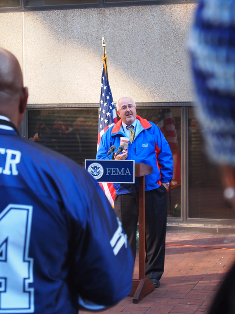 """Washington, D. C. , November 9, 2010 -- FEMA Administrator W. Craig Fugate encourages FEMA employees to give generously to charitable organizations as he kicks off the 2011 Combined Federal Campaign at FEMA Headquarters.  Fugate encouraged staff to consider donating each pay period the amount they spend on their daily cup of coffee.  FEMA staff wore the jerseys and hats of their favorite sports teams as part of the """"Team FEMA"""" theme; Fugate is pictured in a Florida Gators jacket."""