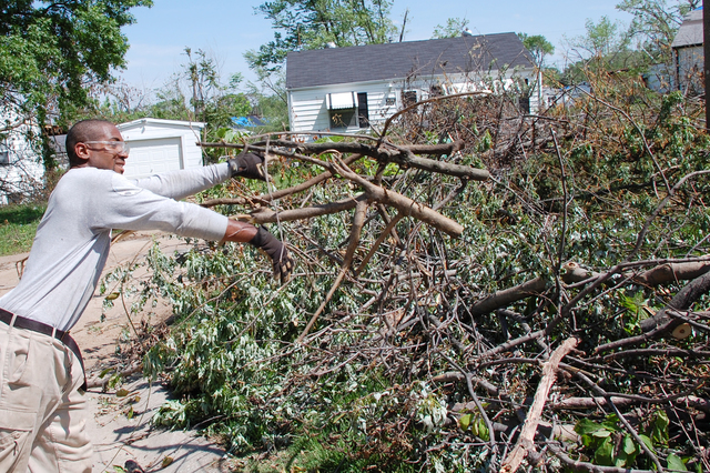 Tornado - Berkeley, Mo. , May 12, 2011 -- Port Jefferson, NY, resident Daquan Staley throws yet another load of debris onto the pile in tornado stricken Berkeley, MO. Staley is an Americorps volunteer doing his second stint helping survivors of U. S. disasters. Berkeley is in the metro St. Louis area and was one of the hardest hit areas following the Good Friday tornado 2011.  Jace Anderson/FEMA
