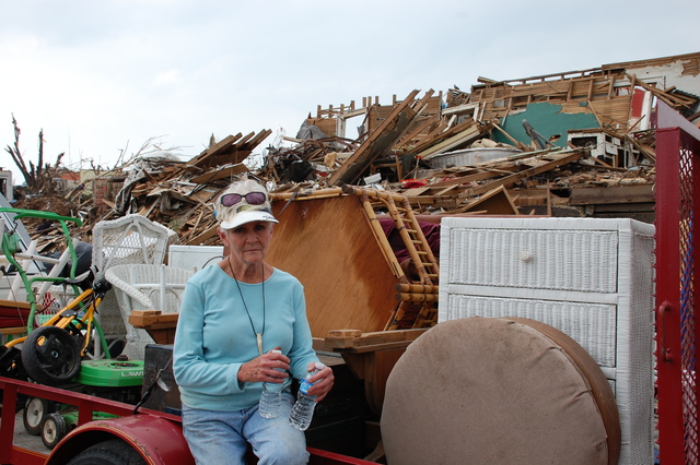 Tornado - Joplin, Mo. , May 24, 2011 -- Barbara A. Bryant sits with the few possessions she, her family and many volunteers were able to rescue from her demolished home. Bryant spent the time as the F5 tornado passed under a basement pool table with her two dogs. The first step for individuals to be considered for temporary housing is to register with FEMA. Jae Anderson/FEMA