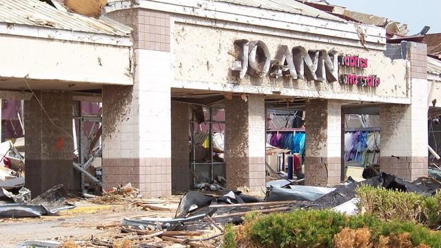 Severe Storm ^ Tornado - Joplin, Mo. , June 7, 2011 -- Brightly colored material is visible through the broken windows and twisted metal of JoAnn Fabrics. The business is one of many In Joplin's business district destroyed by an EF5 tornado on May 22, 2011. FEMA is in the city to support recovery for disaster survivors. Suzanne Everson/FEMA
