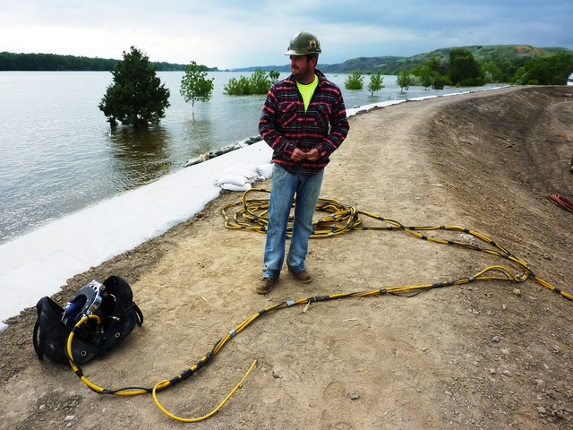 Flooding - Fort Pierre, S. D. , June 8, 2011 -- Dive Supervisor, Nathan Dorman of Adventure Divers, Minot, ND, assesses the flood situation at the levee on the Missouri River, before his team begins plugging drainage culverts. FEMA and other federal agencies are supporting the State Incident Management Team in their effort to respond to the flooding.