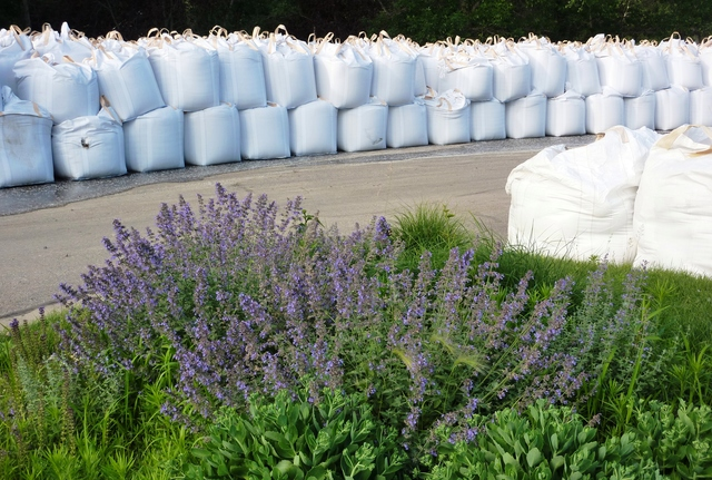 Flooding - North Sioux City, S. D. , June 20, 2011 --This photograph shows stacks of heliobags and beds of lavender side-by-side in the parking lot at Dakota Dunes Country Club on the Missouri River. FEMA and other federal agencies are supporting the State Incident Management Team in their effort to prepare for flooding along the river.