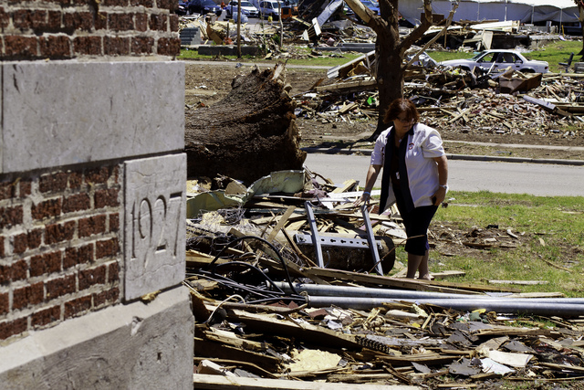Tornado - Joplin, Mo. , June 22, 2011 -- Debbie Fort, Principal of Irving Elementary, looks through the debris left by an EF-5 tornado which destroyed the school, built in 1927. FEMA will reimburse costs associated with retrofitting space for temporary school locations for the start of the new school season. Steve Zumwalt FEMA