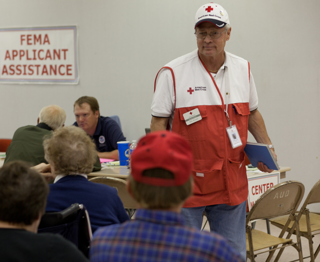 Flooding - Minot, N. D. , June 27, 2011 -- Red Cross volunteer, Phil Wendel talks to disaster survivors at the FEMA/State Disaster Recovery Center in the auditorium in South Minot, N. D. Andrea Booher/FEMA
