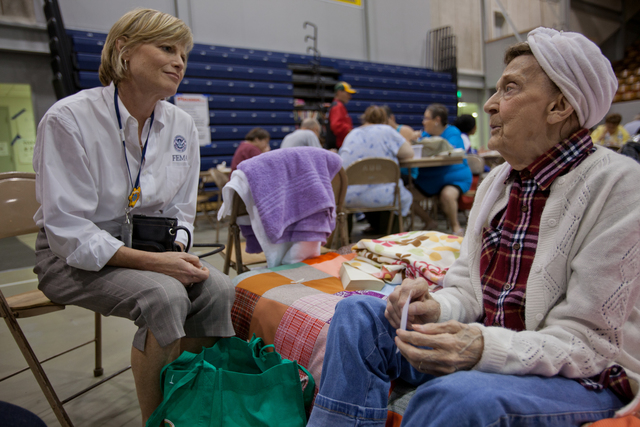 Flooding - Minot, N. D. , June 27, 2011 -- Robin Finegan, FEMA Region VIII Administrator, listens to disaster survivor, Dona Young at the Red Cross Shelter in the Auditorium in South Minot, North Dakota. Andrea Booher/FEMA