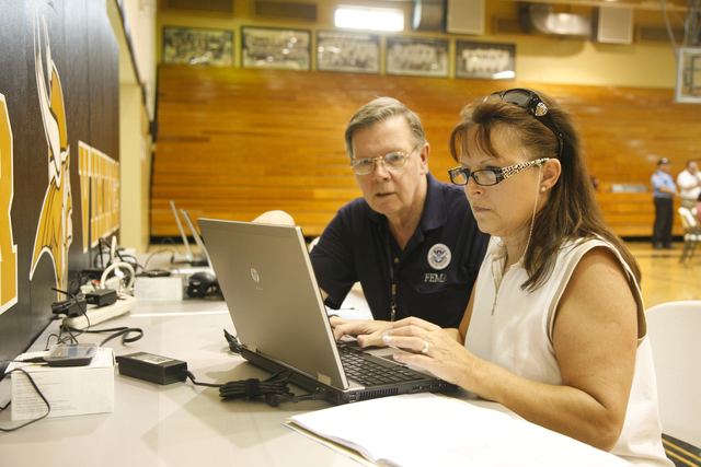 Tornado - Jasper, Ala. , July 9, 2011 -- Housing Expo (held in the gymnasium of Walker High School) to assist disaster survivors recover from the destruction of the tornadoes that struck Alabama on April 27, 2011. FEMA Information Technology specialist Walter Corbiere assists Debra Standord register online for FEMA assitance.  Photo by Christopher Mardorf / FEMA.